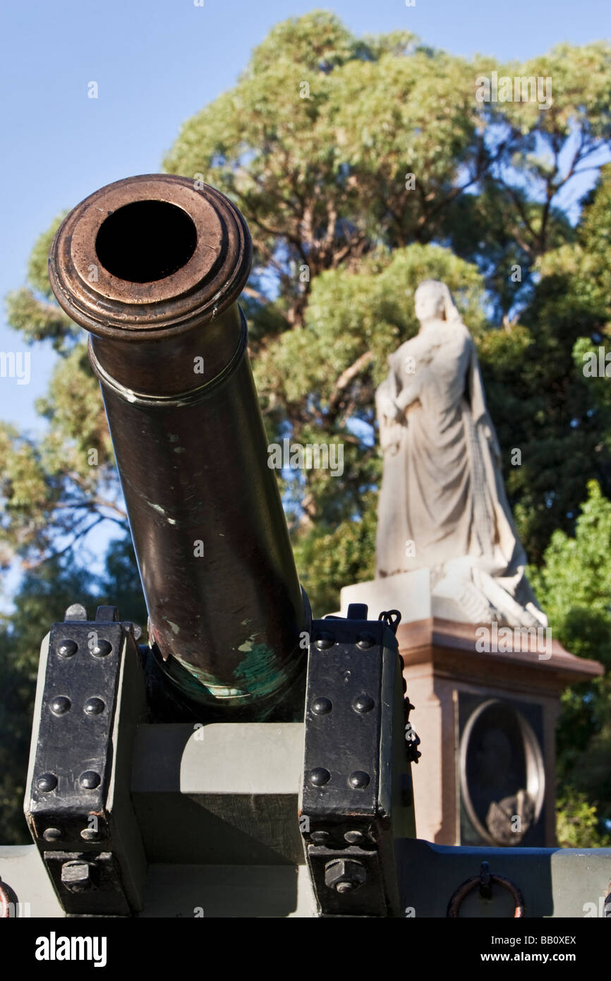A cannon and statue of Queen Victoria. Empire, imperialism, colonialism, War and conquest concept. - Stock Image