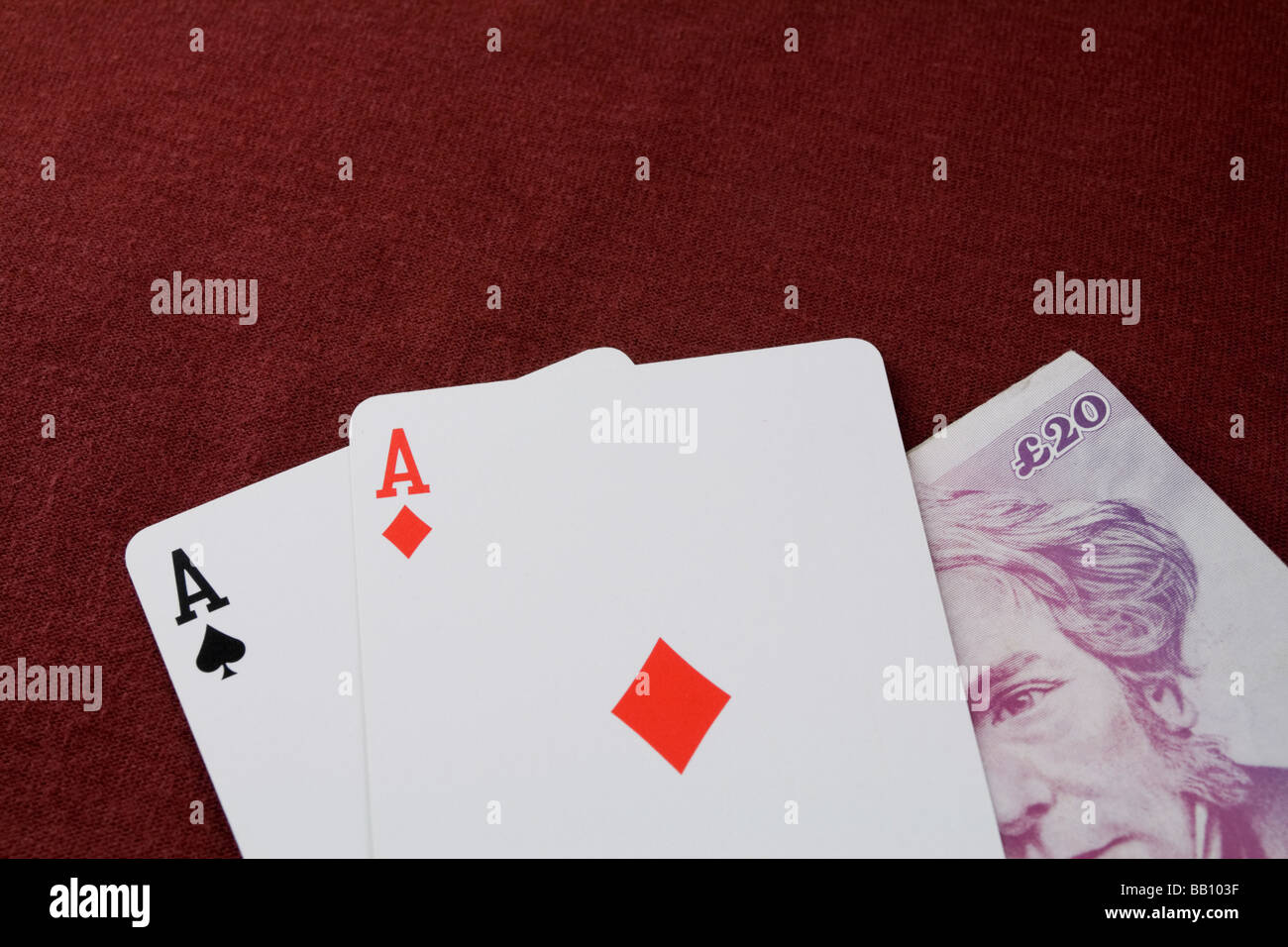 Ace of spades and ace of diamonds over 20 pound note - Stock Image