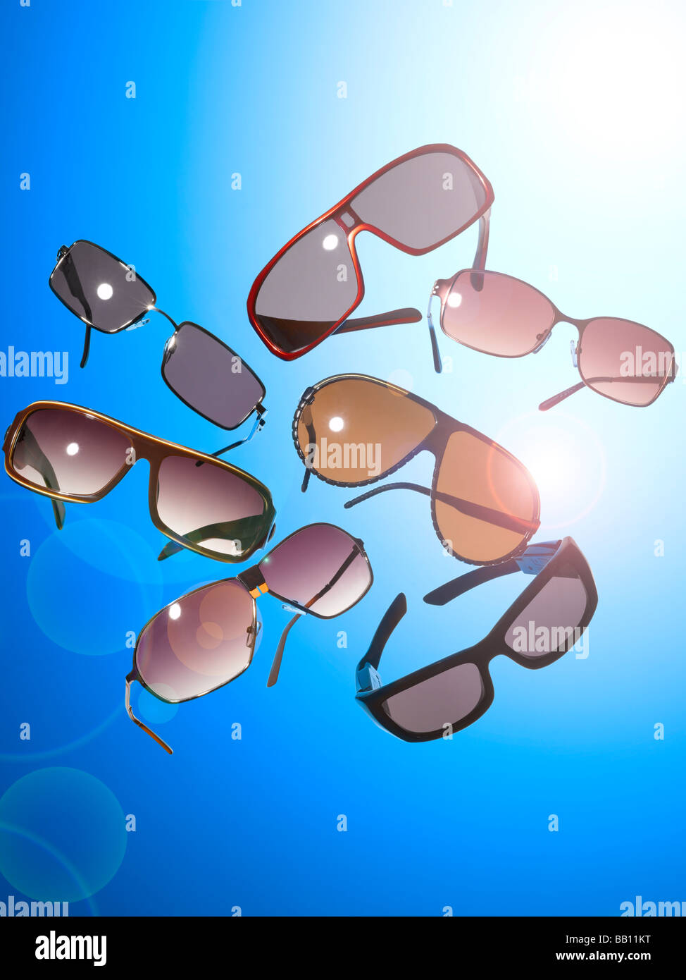 A collection of sun glasses on a blue background - Stock Image