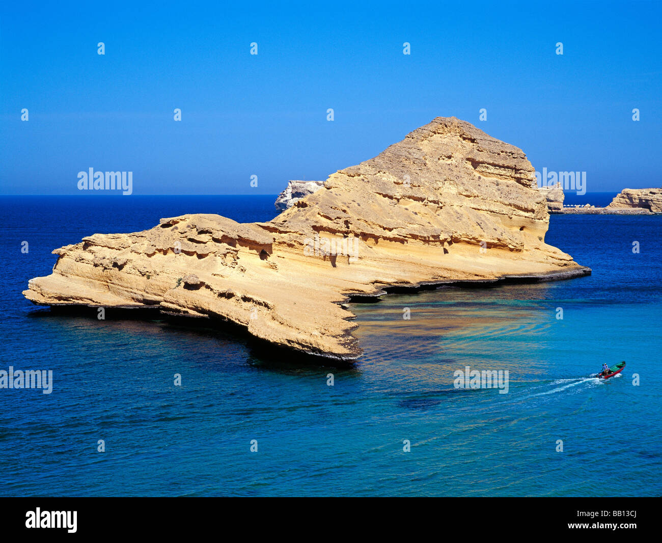 fisher boat crossing in front of a big rock in the blue Arabian Sea Stock Photo