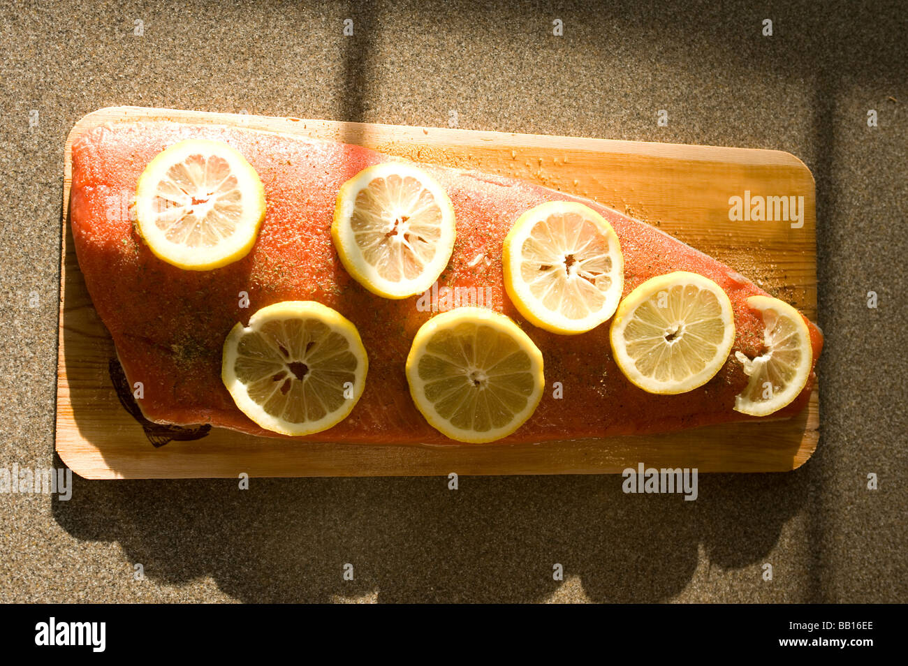 A fillet of sockeye salmon is seasoned and lying on a water soaked cedar plank and ready for the grill - Stock Image