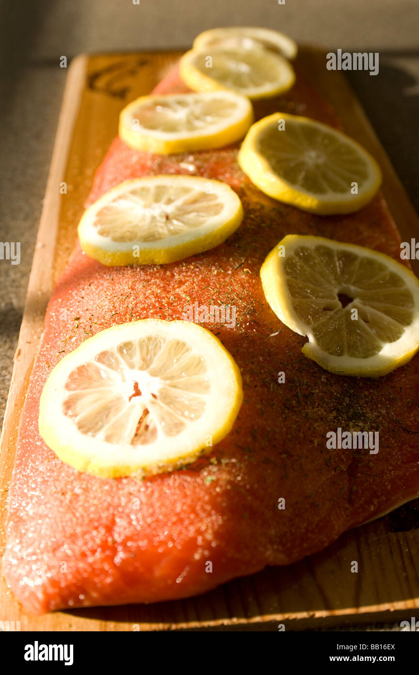 A fillet of sockeye salmon is pictured on a water soaked cedar plank on which it is baked on a grill - Stock Image