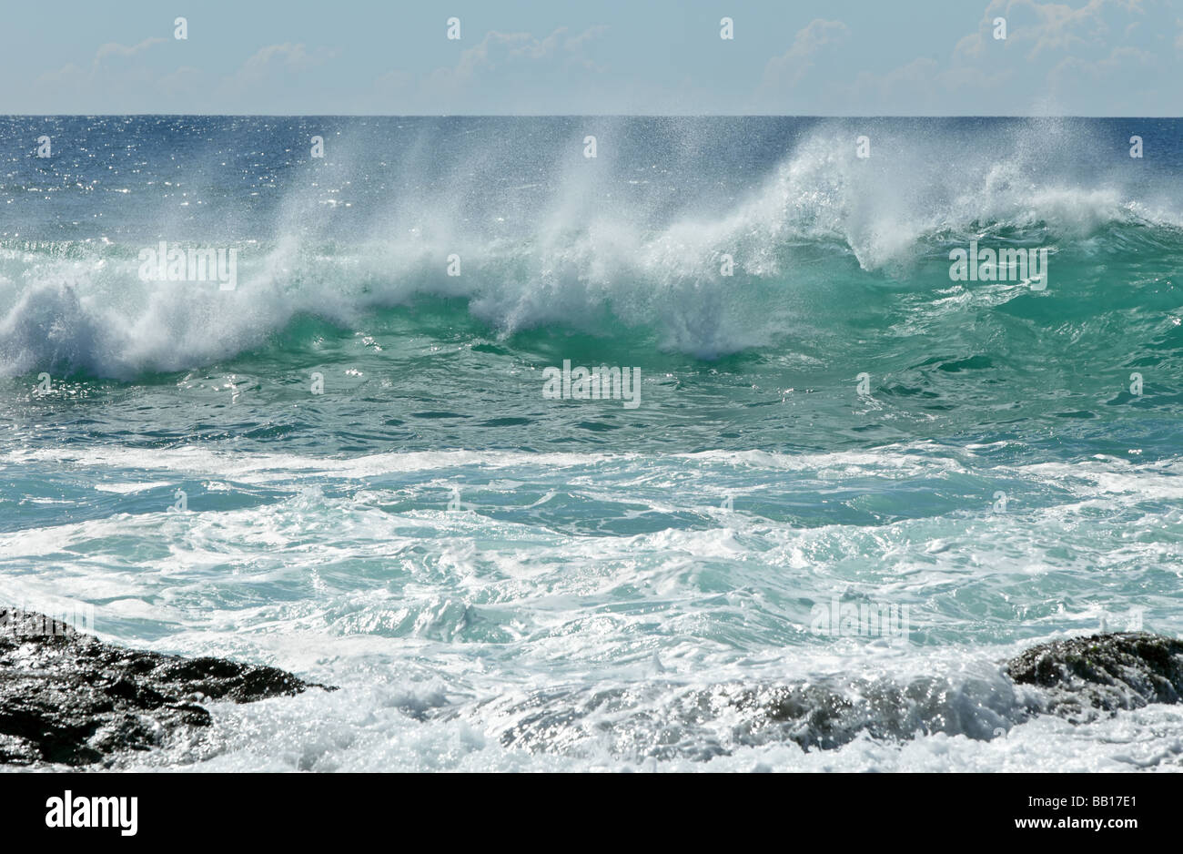 Waves breaking near rocks - Stock Image