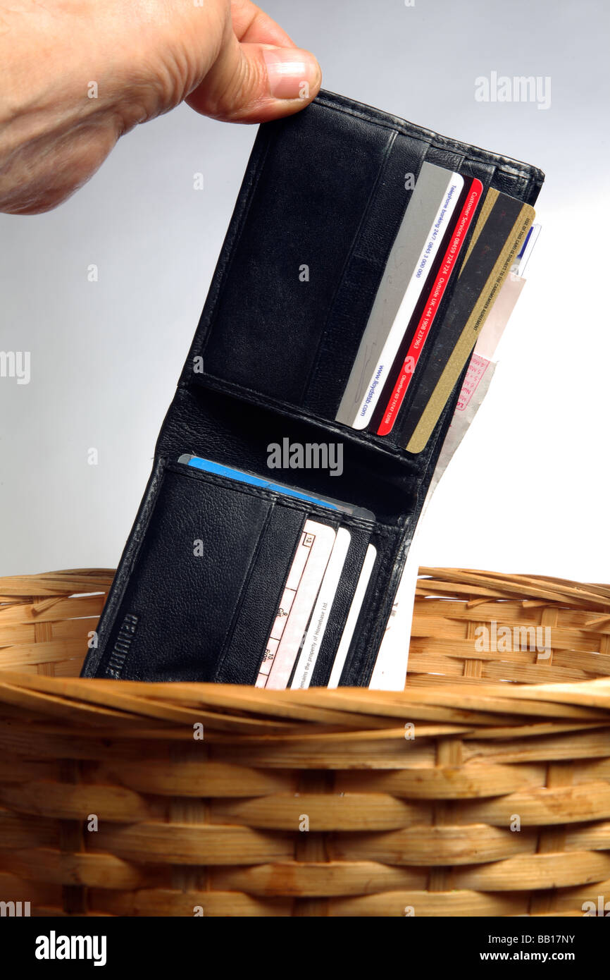 Wallet dropping into waste basket. - Stock Image