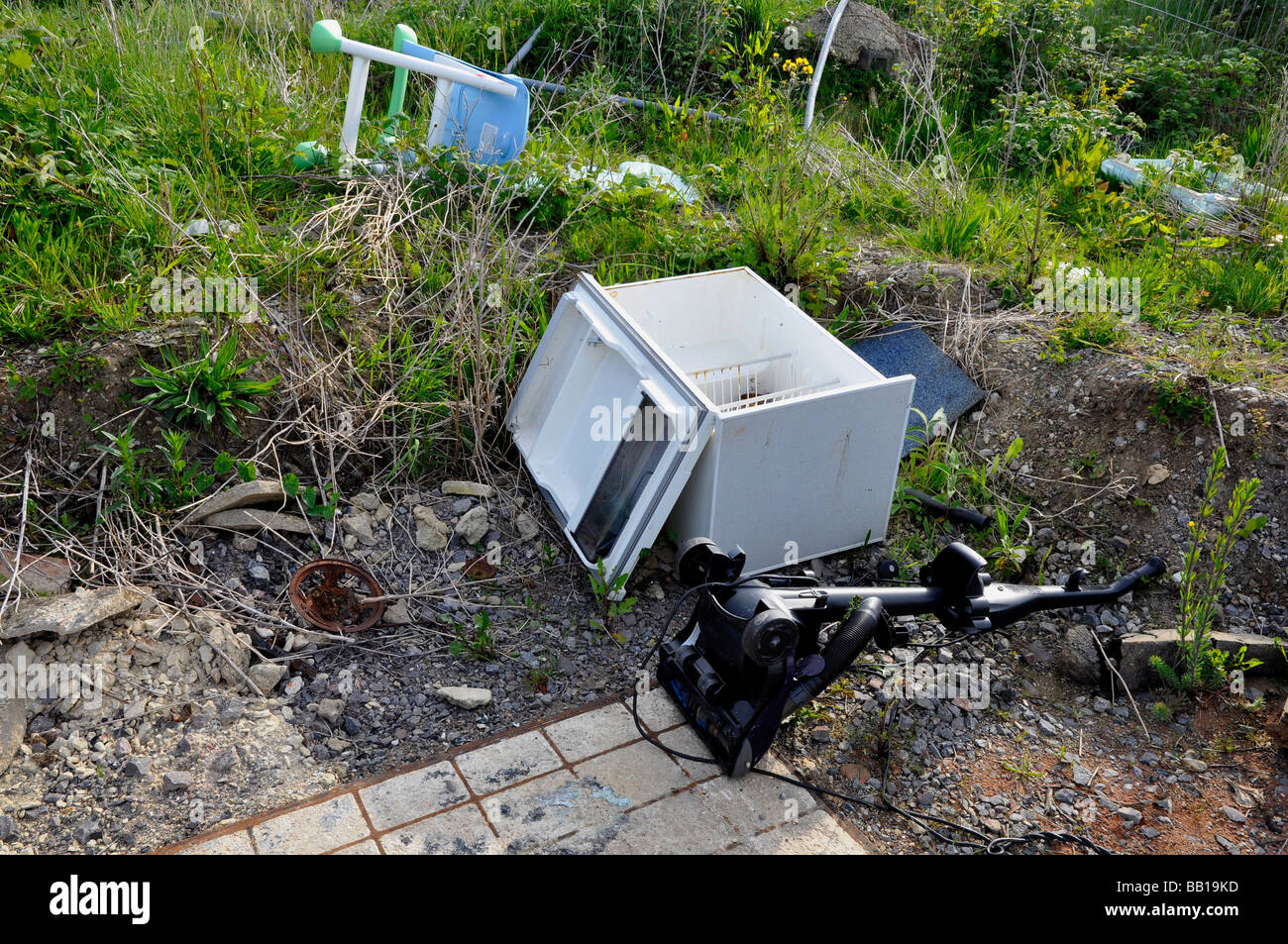 Fly-Tipping - including an old fridge - Stock Image