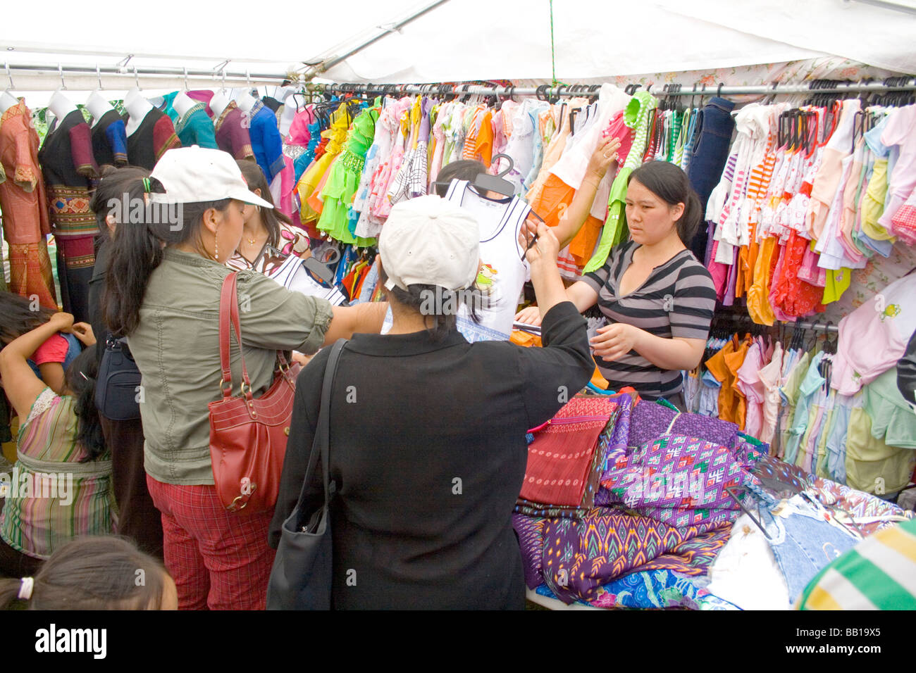 Hmong SE woman shopping for children's clothing in busy tented shop. Hmong Sports Festival McMurray Field St - Stock Image