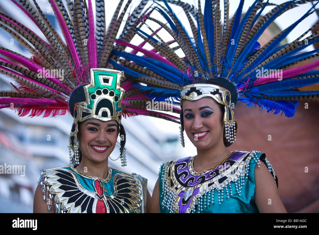 Two women in Aztec outfits, wearing feather headdress with Pheasant feathers, Cruise Ship Terminal; Mazatlan, Sinaloa, - Stock Image