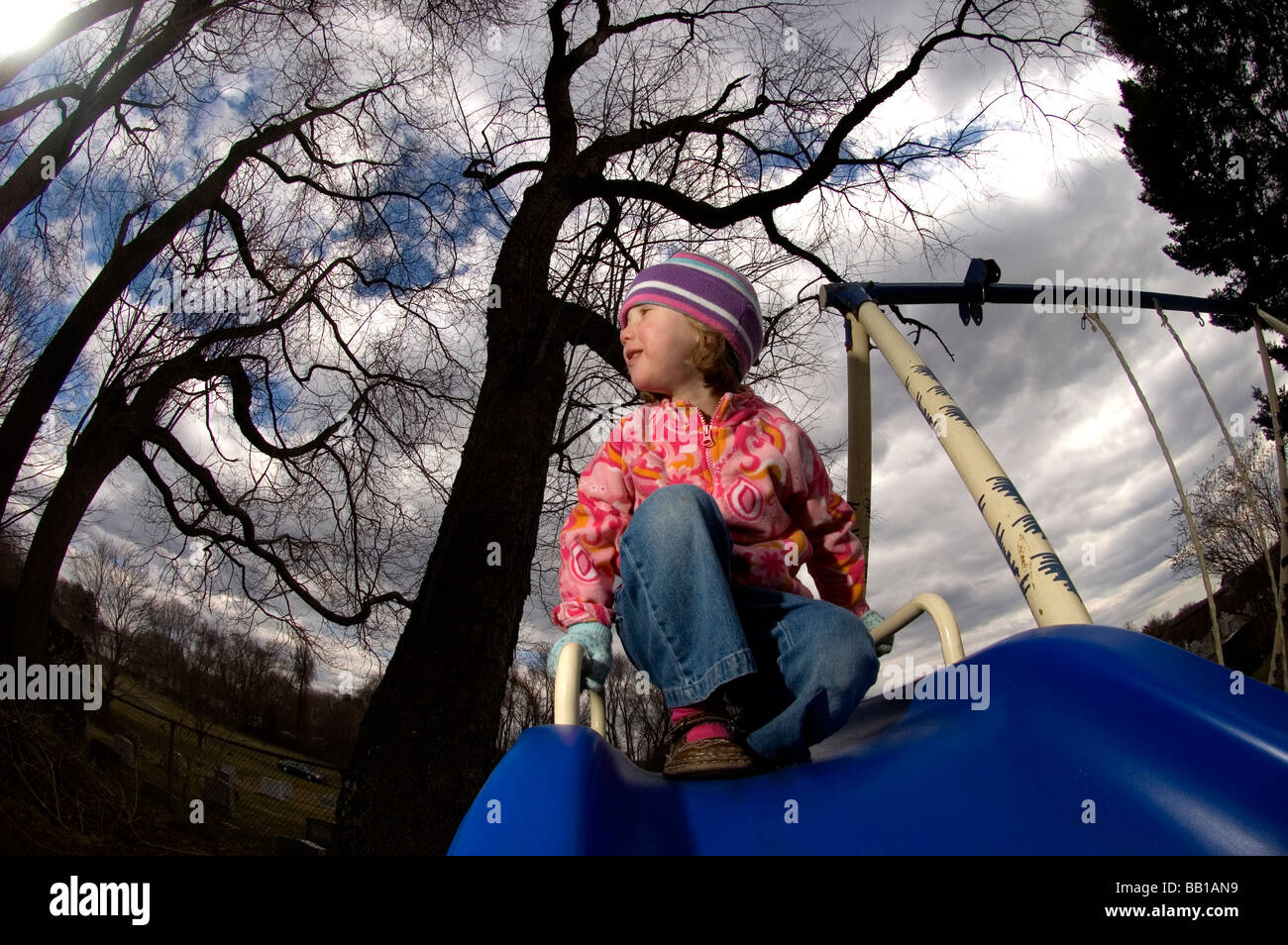 A young girl gets ready to go down a slide during a cool crisp day. - Stock Image