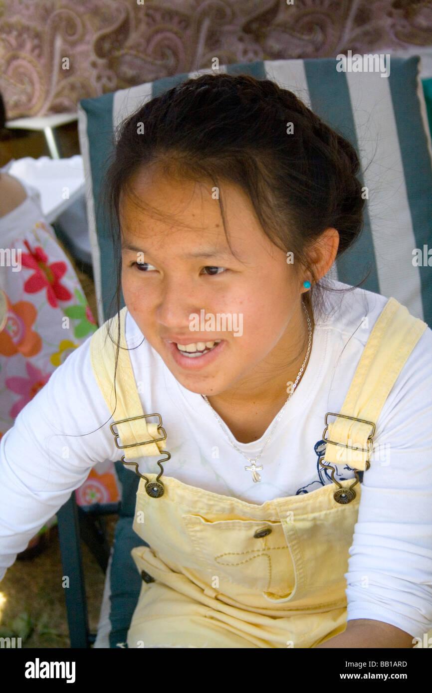 Happy teenage festival worker wearing yellow bibs. Hmong Sports Festival McMurray Field St Paul Minnesota USA - Stock Image