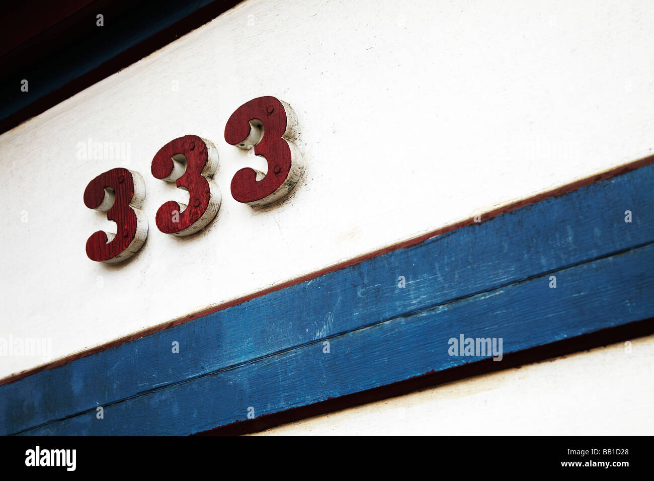 333 on white wall, 333 red - Stock Image