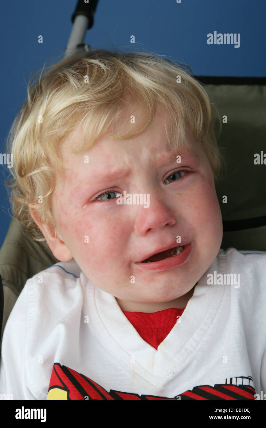 Blonde haired child crying with tears in his eyes. - Stock Image