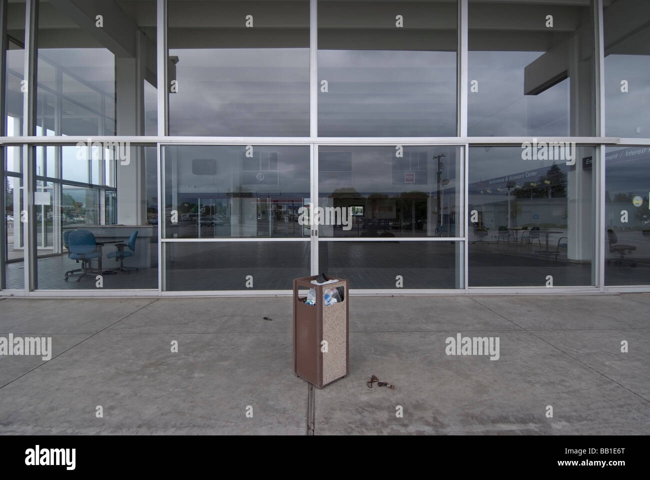 Waste can sits in front of the empty showroom of a closed Buick Pontiac GMC Dealership in San Jose,CA. - Stock Image