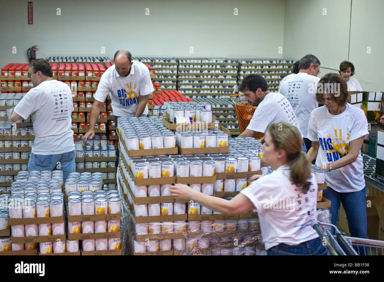 Volunteers stacking up and organizing cans in the warehouse of the California Food Bank in Garden Grove, California - Stock Image