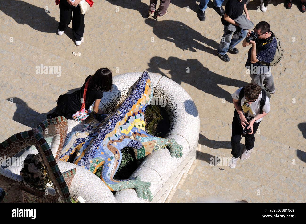Tourists at Antoni Gaudis Dragon Sculpture in Parc Güell, Barcelona Spain - Stock Image