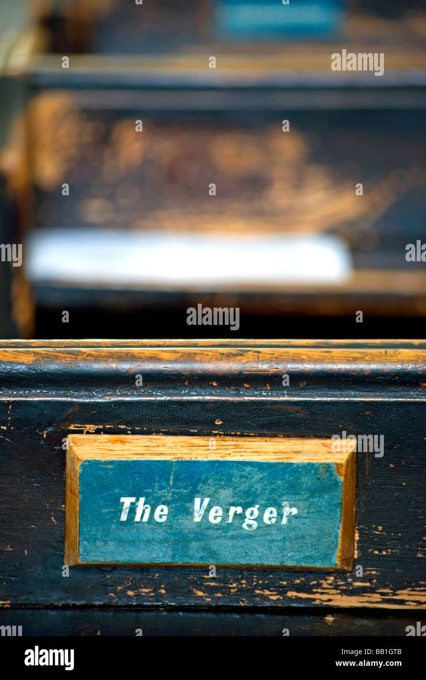 sign on back of british church pew showing seat reserved for the verger - Stock Image