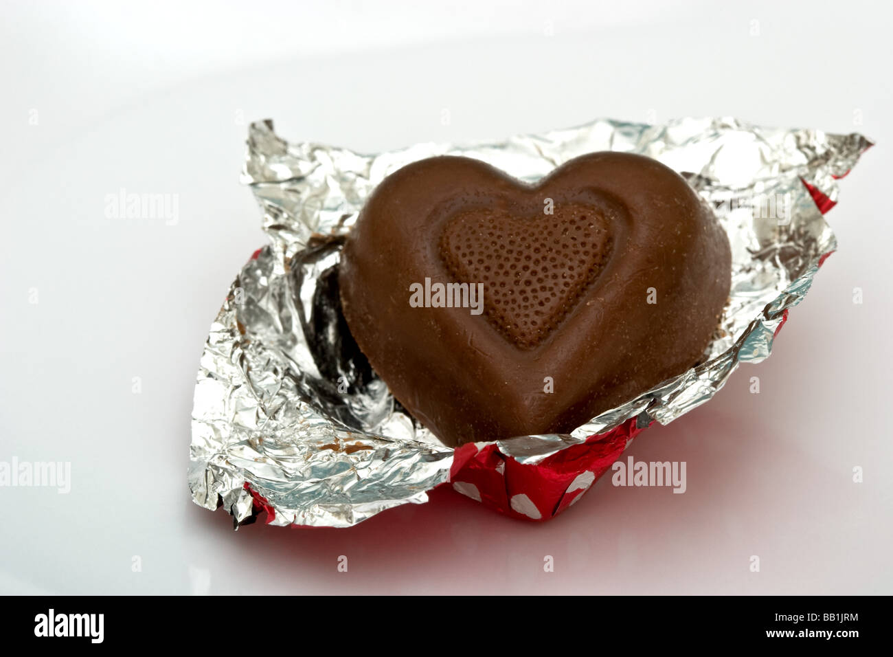 Single heart shaped chocolate candy in aluminum foil wrapping - Stock Image