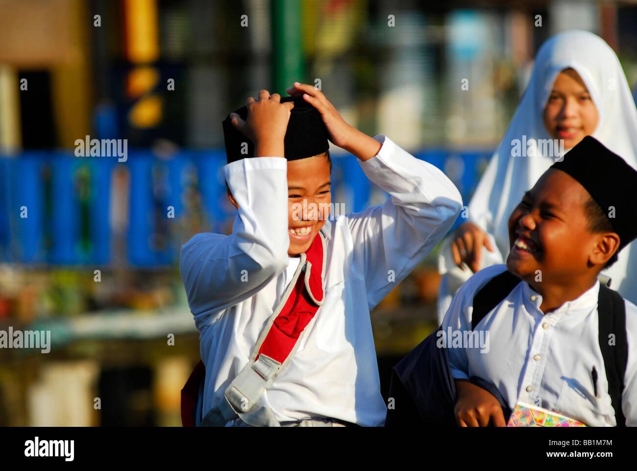 BRUNEI, Bandar Seri Begawan. Portrait of asian muslim schoolboys wearing white shirt, playing - Stock Image