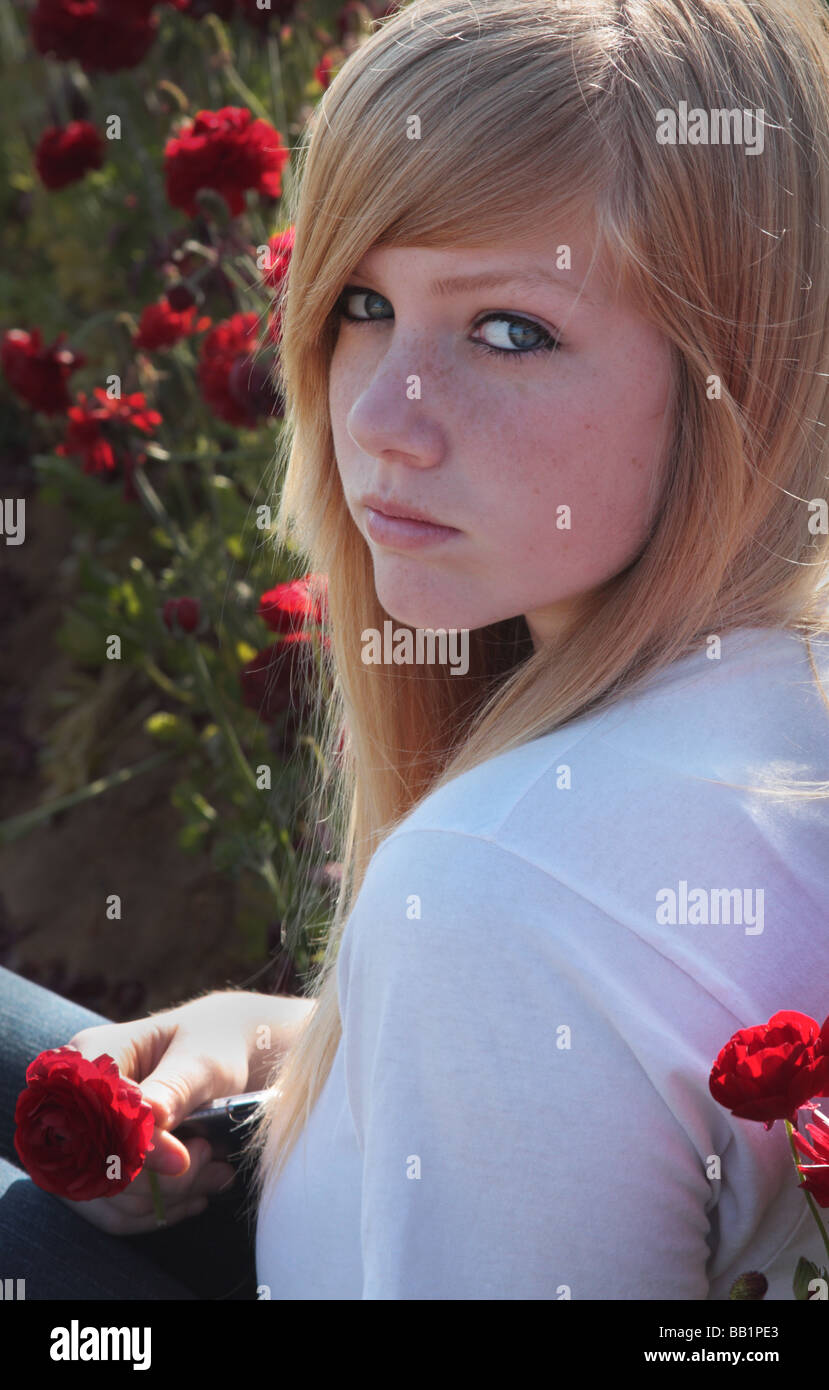 USA A portrait of a beautiful teenage girl looking directly at the camera and sitting in a field of red flowers - Stock Image