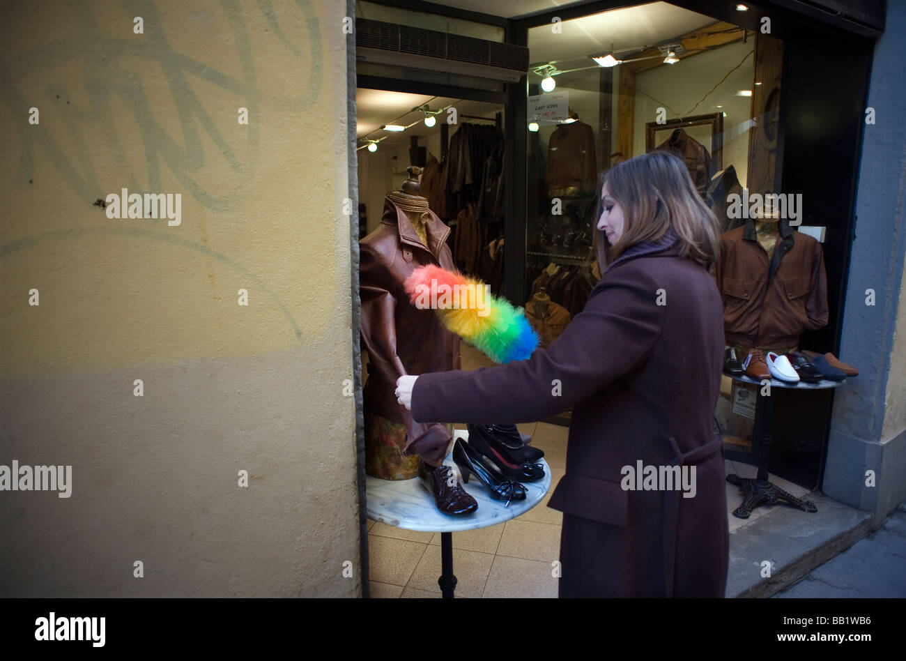 Florence Tuscany Italy The city of the Renaissance Photo shows Shopkeeper dusting her leather goods from dust and - Stock Image