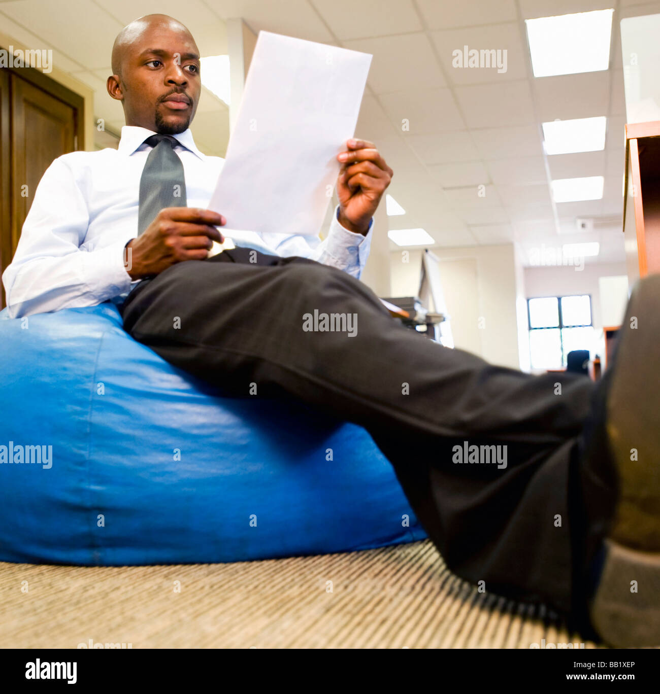 Businessman relaxes with a business report on a bean bag. Pretoria, South Africa Stock Photo