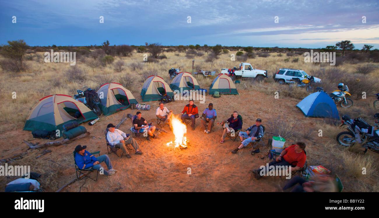 Bikers sit around a fire at camp, Central Kalahari Desert, Botswana - Stock Image