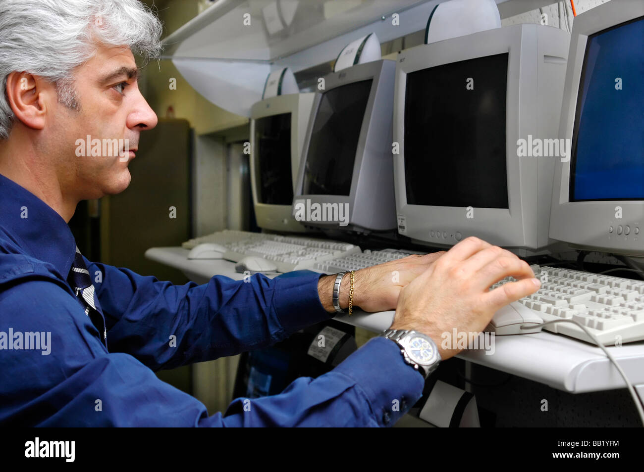 Technician looking at a computer screen and entering data - Stock Image