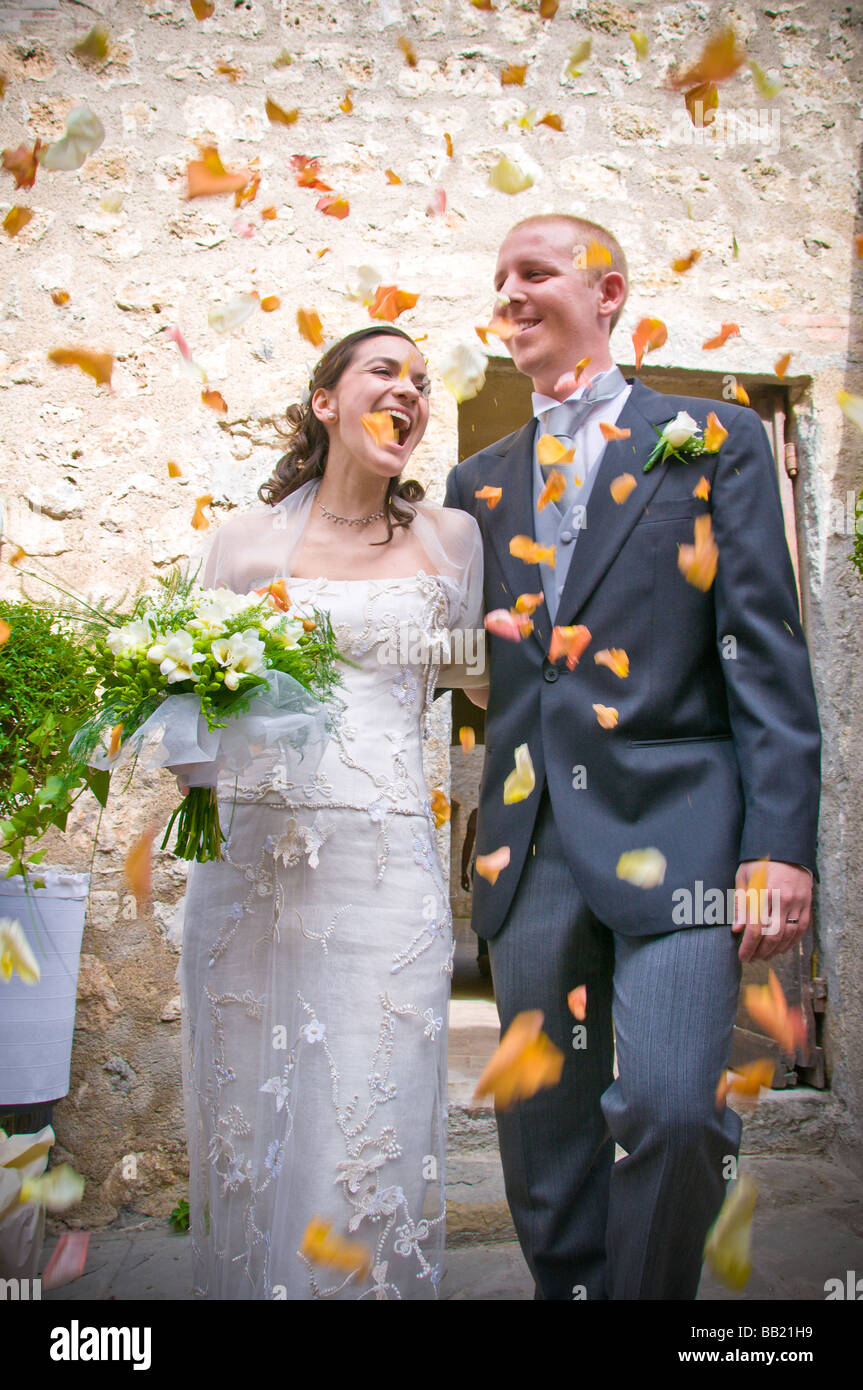 Newlywed couple with thrown flower petals after service - Stock Image