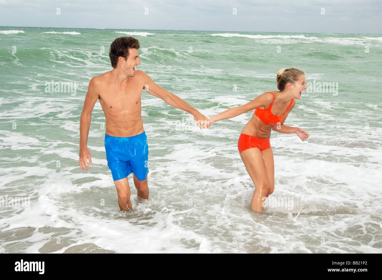 Couple holding hands and walking in water on the beach Stock Photo