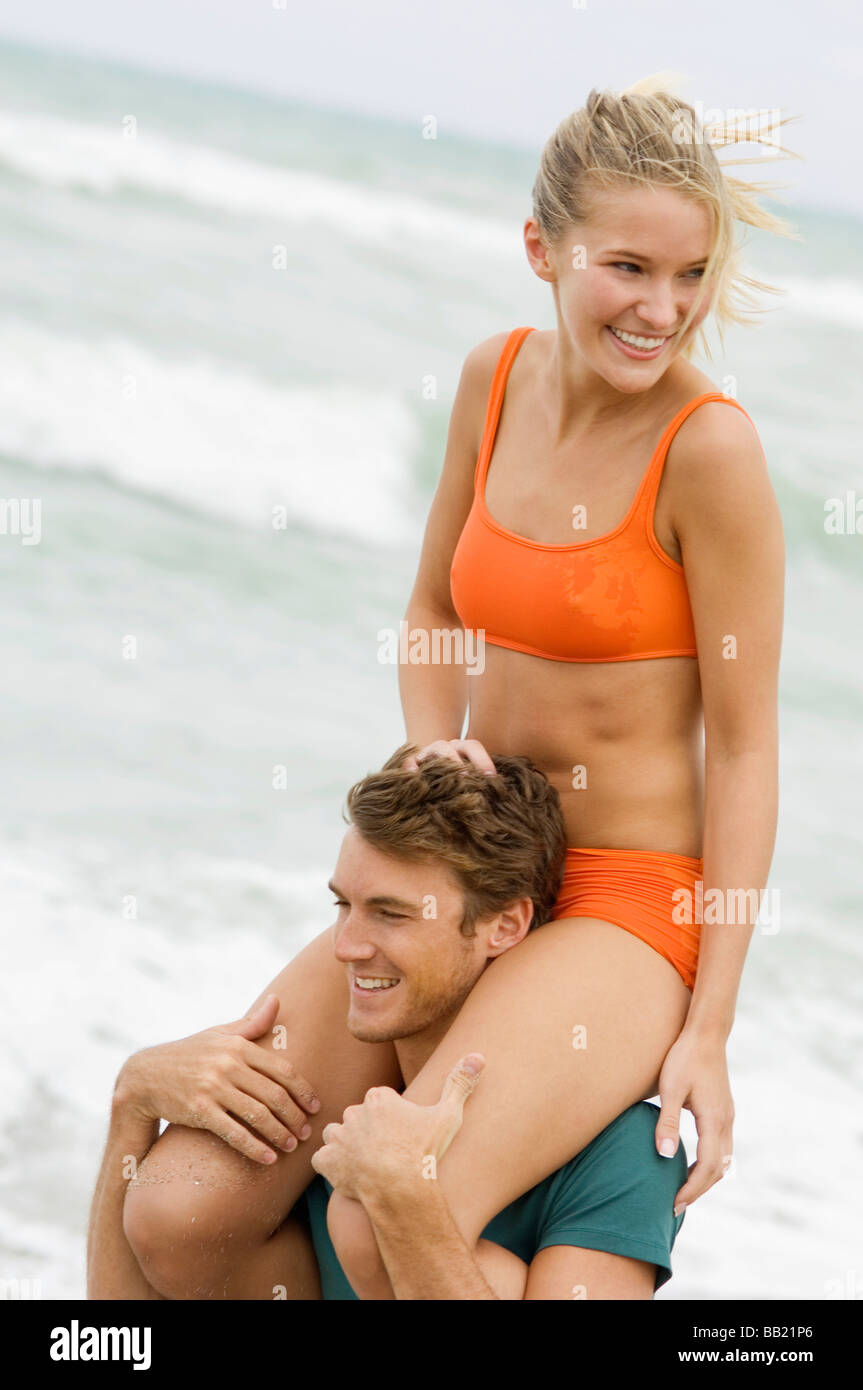 Man carrying a woman on his shoulders on the beach - Stock Image