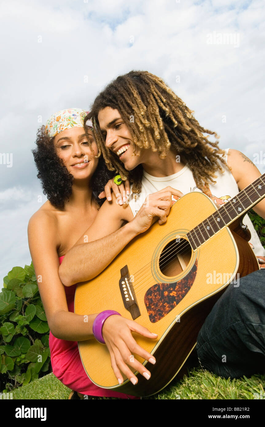 Couple playing a guitar - Stock Image