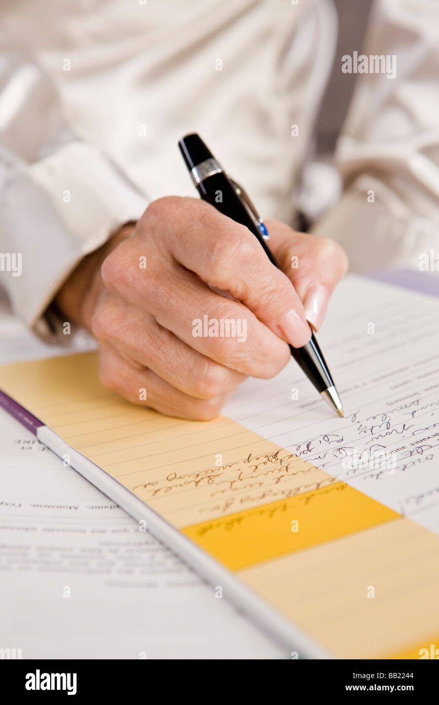 Mid section view of a woman filling out an application form - Stock Image