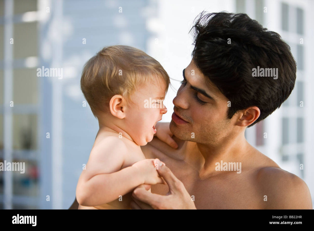 Man consoling his crying son - Stock Image