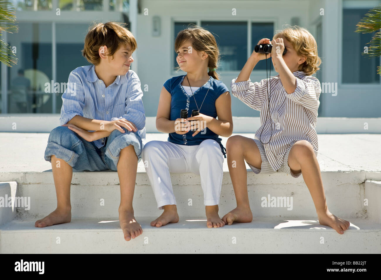 Boy looking through binoculars with his friends sitting beside him - Stock Image