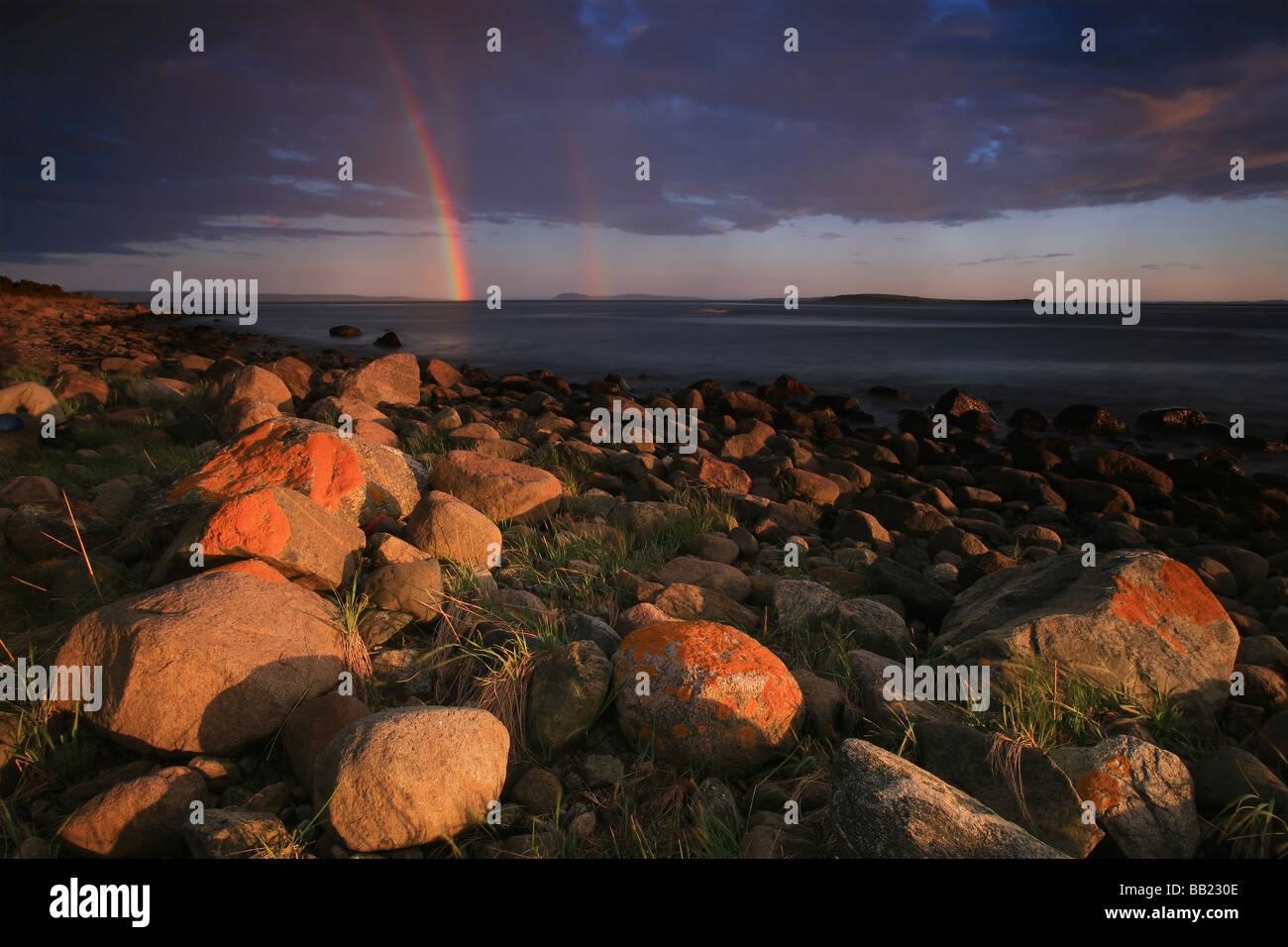 Beautiful evening light and rainbow by the Oslofjord at Larkollen, Østfold fylke, Norway. - Stock Image