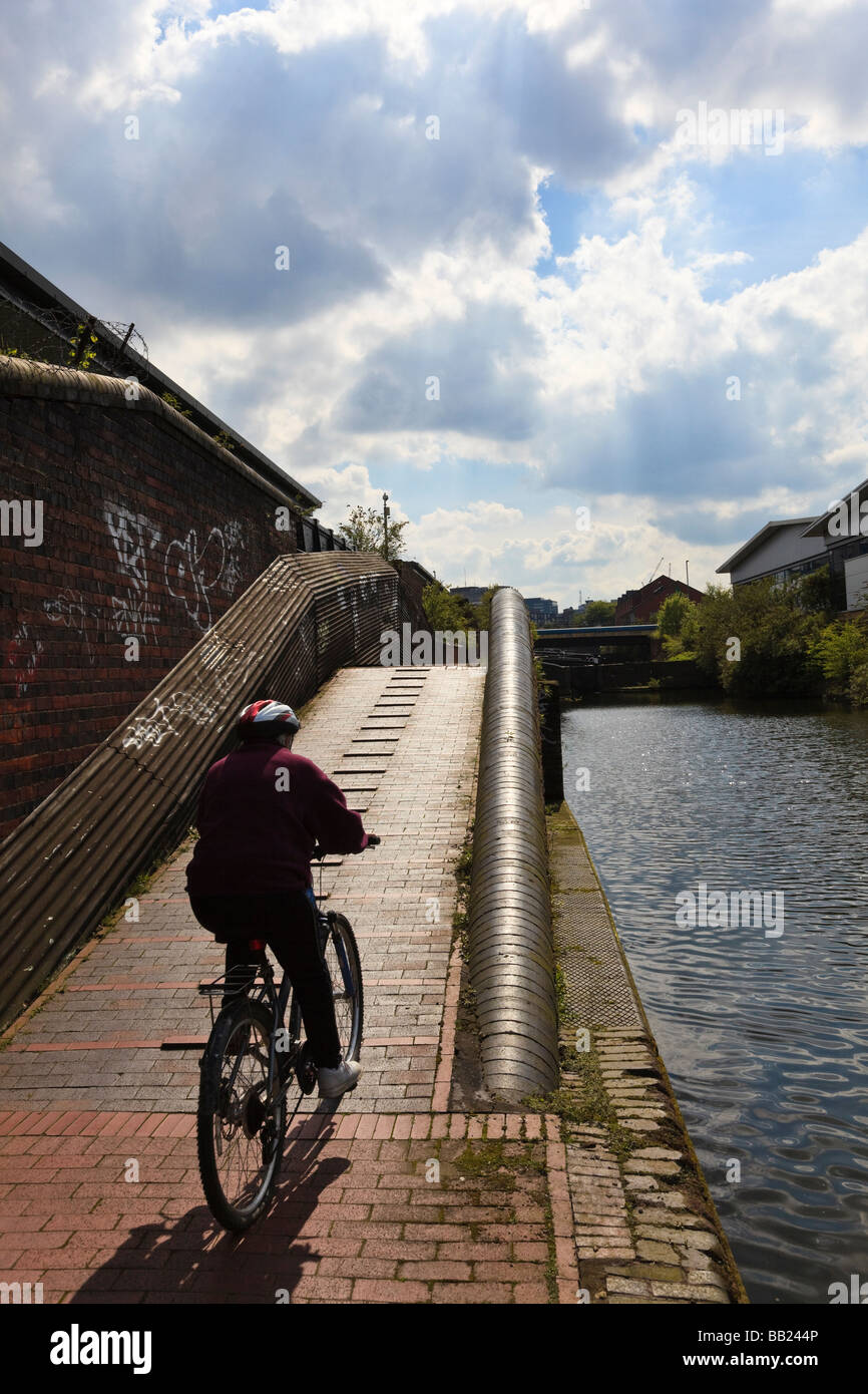 (Sequence 1 of 3)Cyclist riding along the towpath of The Birmingham and Fazeley Canal at Aston - Stock Image