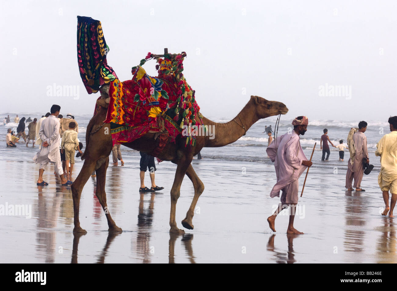 Pakistani s enjoying the camels and the sea on Clifton beach Karachi Pakistan - Stock Image