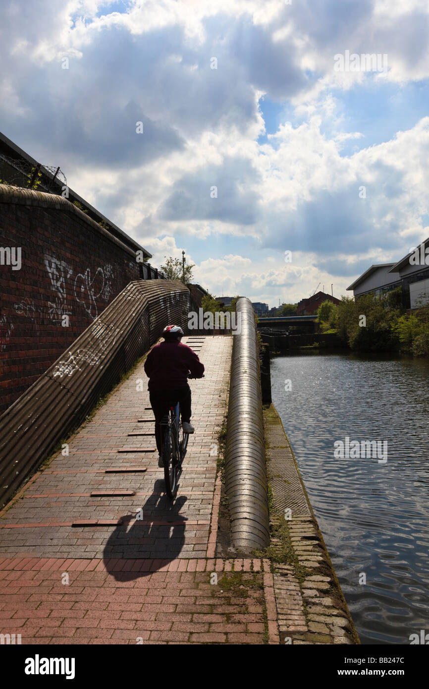 (Sequence 2 of 3)Cyclist riding along the towpath of The Birmingham and Fazeley Canal at Aston - Stock Image
