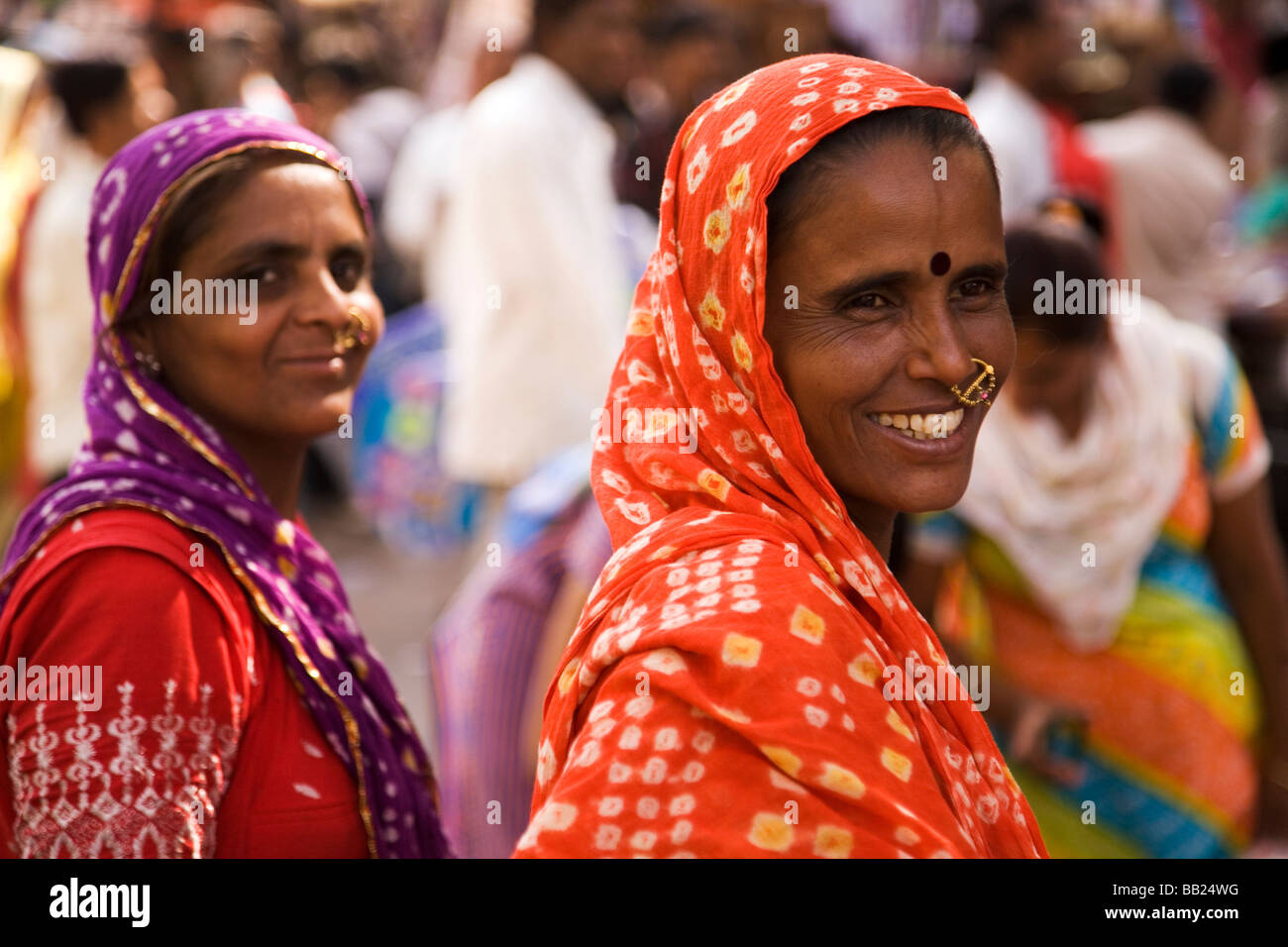 Two colourfully dressed women stand together in a market in the old city of Ahmedabad, Gujarat - Stock Image