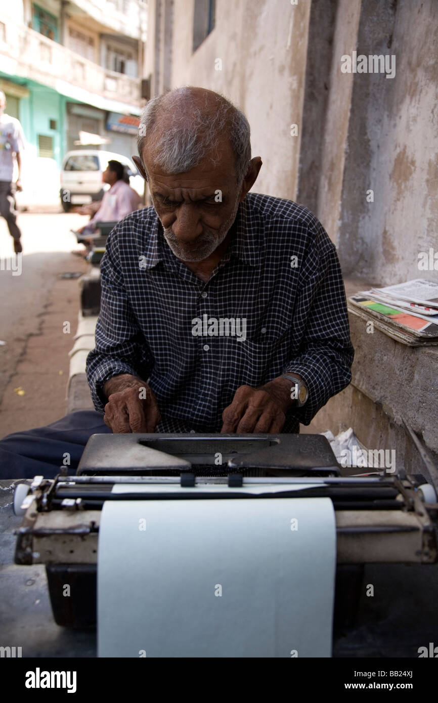 A man sits on the street working on a typrewriter in the heart of the old city of Ahmedabad, Gujarat. - Stock Image