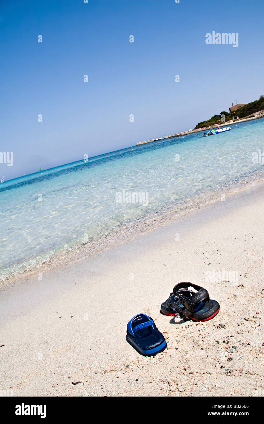 two different sandals on the sand in front of the sea, Stintino, island, Sardenia, Italy - Stock Image