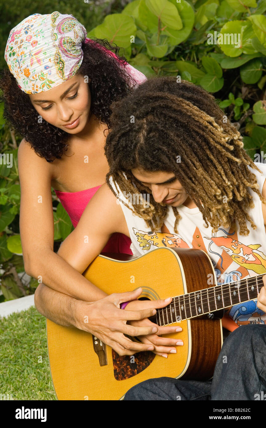 Man teaching a woman how to play a guitar - Stock Image
