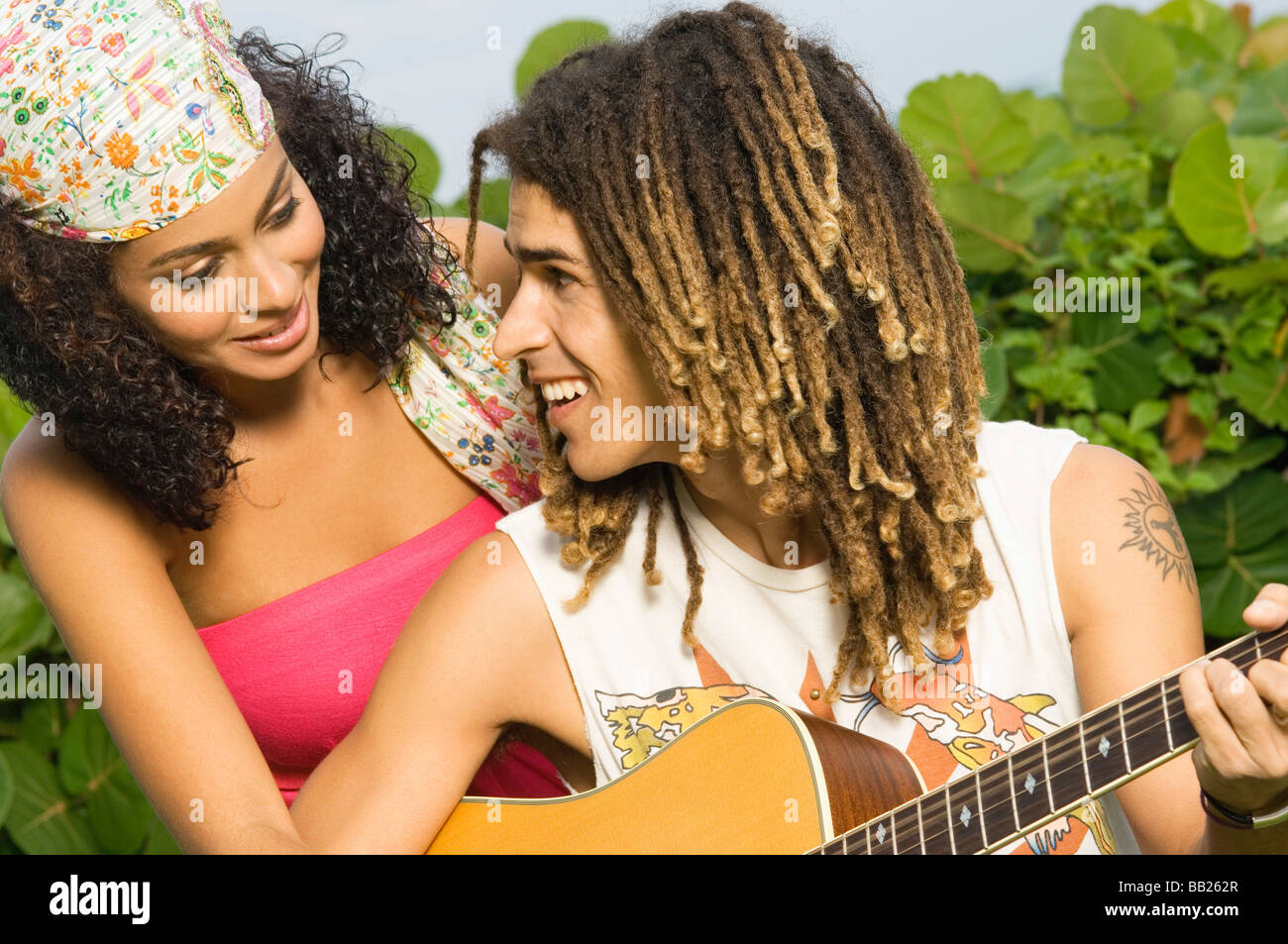 Couple playing a guitar and smiling at each other - Stock Image