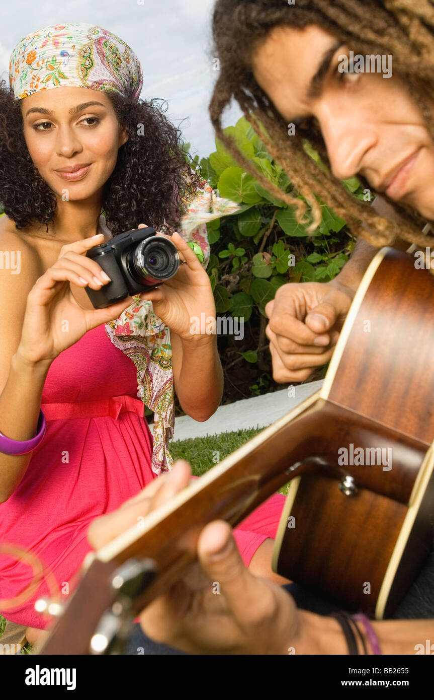 Woman taking a picture of a man playing a guitar - Stock Image
