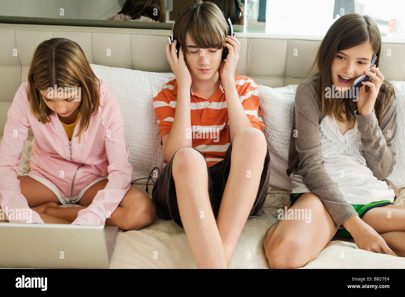 Boy Sitting With Two Girls On The Bed Stock Photo 24021372 Alamy