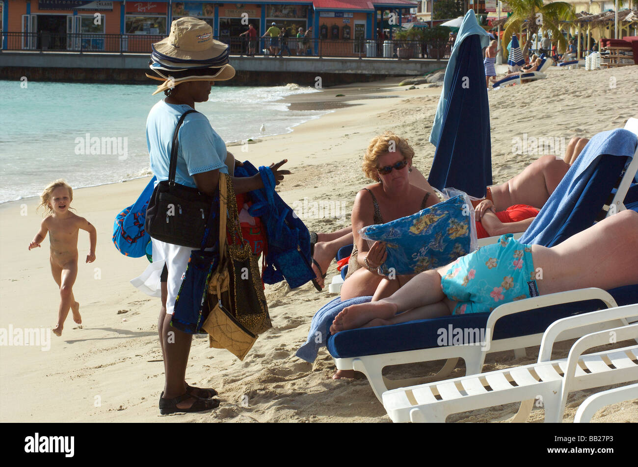Sint Maarten immigrant selling hats on the beach - Stock Image