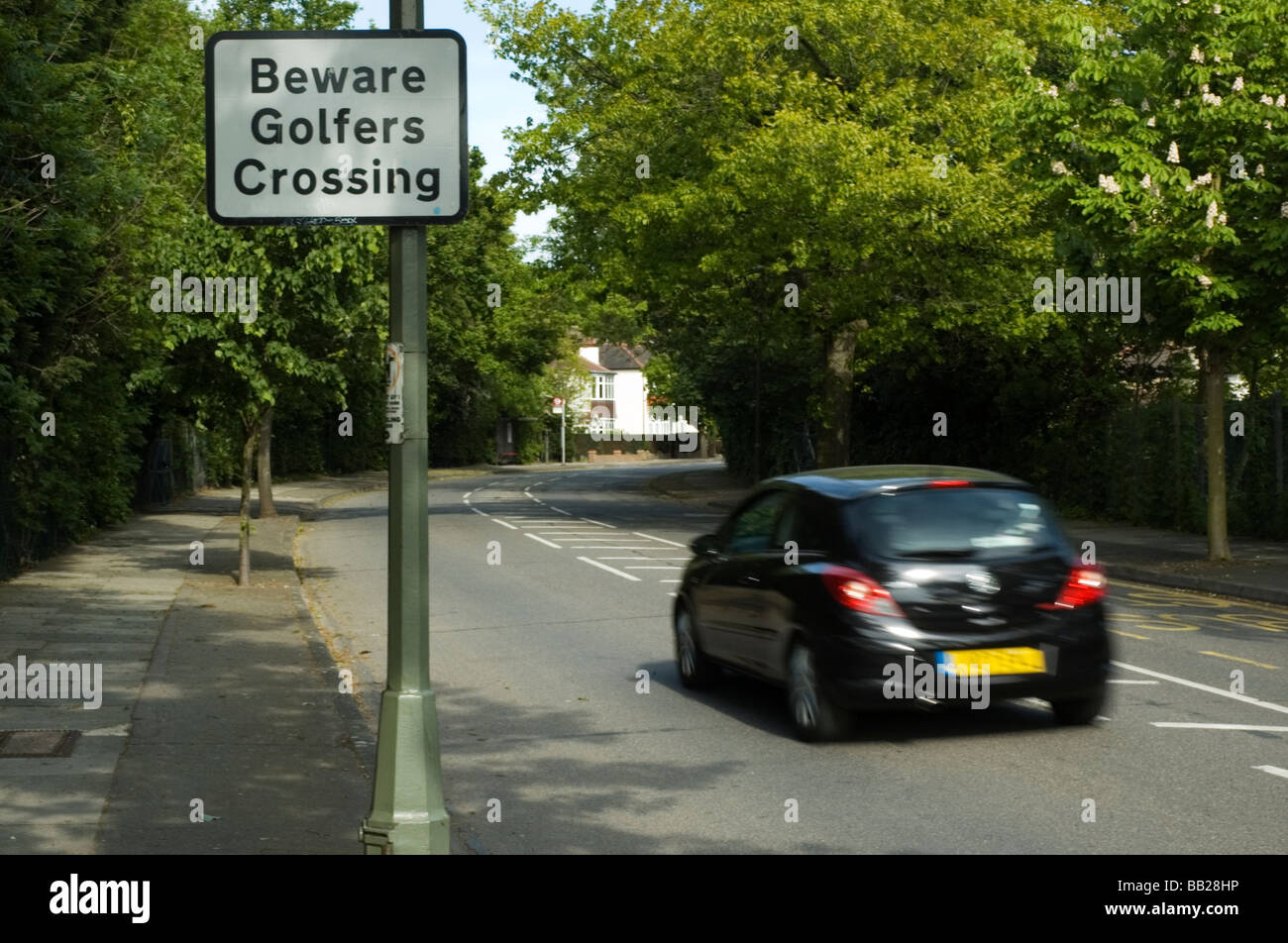 A road sign warns approaching traffic of golfers crossing a suburban road between two sections of Shortlands Golf - Stock Image