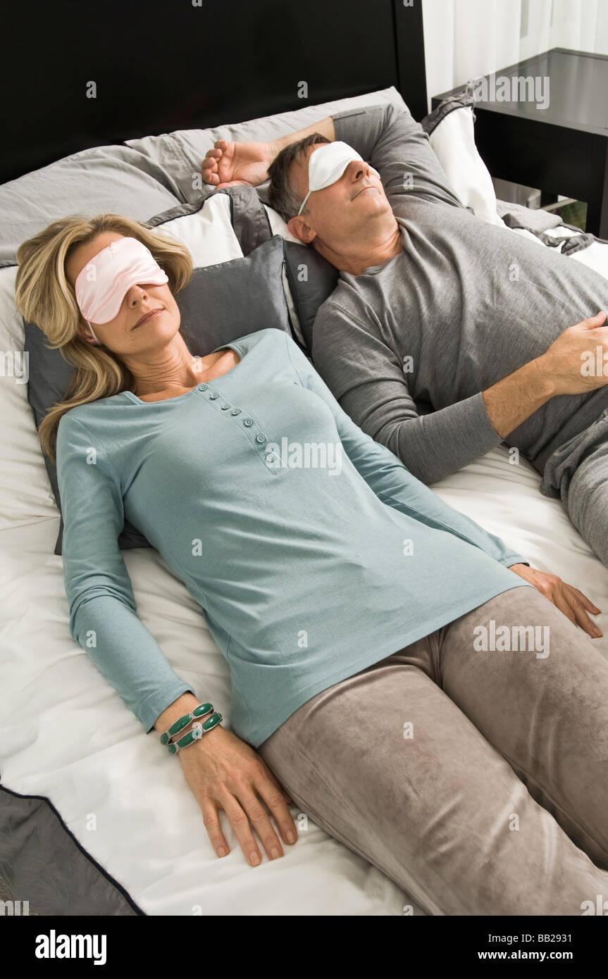 Couple sleeping in bed wearing eye masks - Stock Image