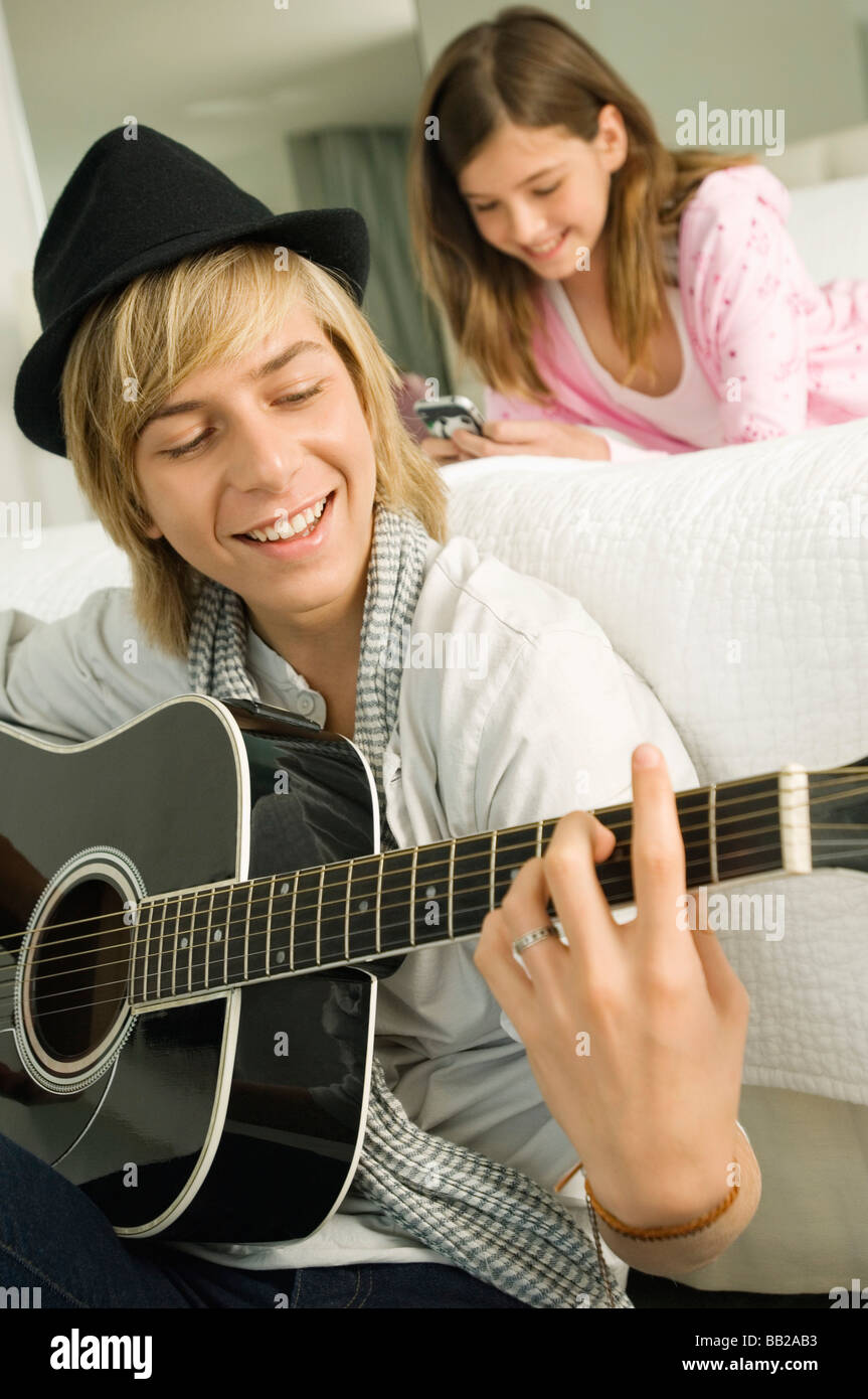Teenage boy playing a guitar and his sister using a mobile phone behind him - Stock Image