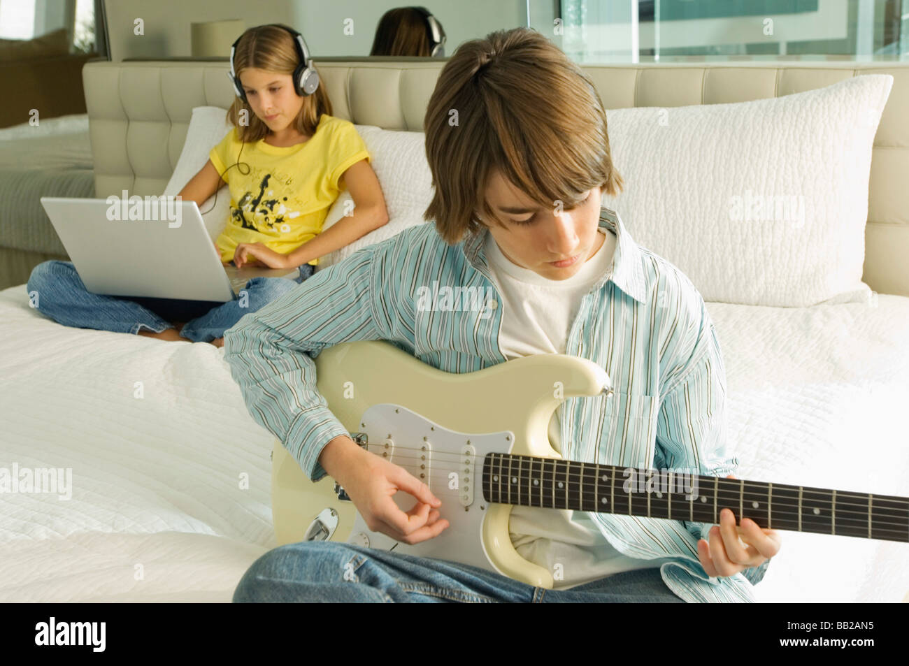 Boy playing a guitar and girl working on a laptop behind him - Stock Image
