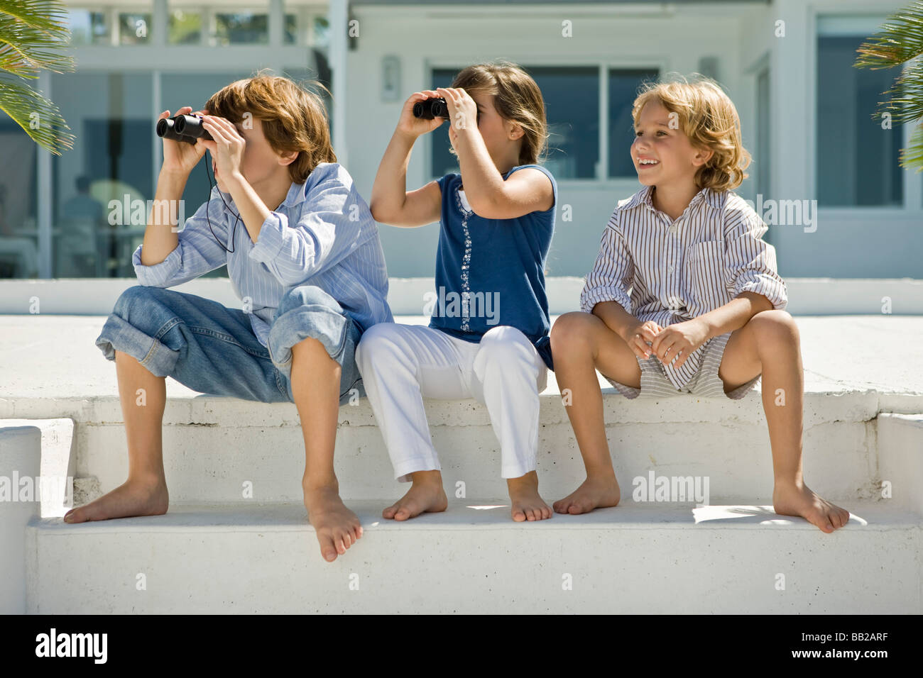 Two children looking through binoculars with their friend sitting beside them - Stock Image